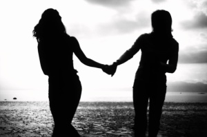Dos mujeres tomadas de la mano en la playa, en silueta